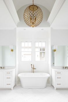 All white master bathroom with a freestanding tub + windows over the tub + Brass round orb chandelier over the tub + brass sconces mounted onto the mirrors Bathroom Chandelier, White Chandelier, Bathroom Curtains, Bathroom Lighting, Master Tub, White Master Bathroom, Master Bathrooms, Best Bathroom Designs, Bathroom Ideas