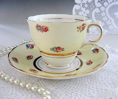 Sweet yellow English bone china tea cup and saucer set made by Colclough of Longton, England. Little cottage style roses on pale yellow over a snow white ground. Lots of gold gilt trim adds just the right dressy touch. Matching backstamps date the set to the 1940s. It would make a beautiful gift...for yourself or someone very special. Standard size.  Absolutely no damage, crazing or wear...appears to have never been used.  ❖ Manufacturer: Colclough ❖ Country: England ❖ Pattern: Cottage Roses…