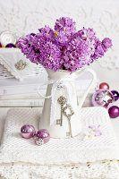 Violette Hyazinthen in Vintage Kanne mit Christbaumkugeln auf Spitzendecke