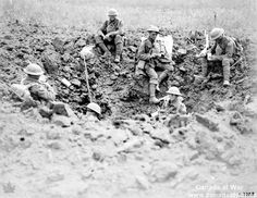 Resting in a Shell Hole - Exhausted Canadians rest in a shell hole during the Battle of Amiens in 1918. These six infantry soldiers must be far from the front lines as several soldiers are sitting dangerously exposed.