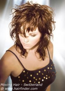 Bounce, shine and asymmetrical effects are the ingredients to a super modern haircut that also shows a romantic side with its large curls. The hair is evenly layered starting at eye level. Bangs are cut asymmetrical with choppy short and wispy longer parts. A yummy chocolate brown is highlighted with golden blonde accents. Crush hair with fingers and mousse to achieve curly effects