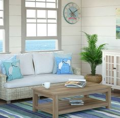 Beach cottage style with white wicker sofa, blue wave rug and shorebird pillows... shop the look: http://www.beachblissdesigns.com/2017/03/beach-decor-living-room-with-white-wicker-sofa.html