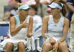Anna Kounikova of Russia and Martina Hingis of Switzerland confer while playing Tatiana Perebiynis of the Ukraine and Tatiana Poutchek of...