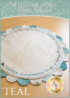 """Welcome Home Table Topper - Teal Kit: This Welcome Home Table Topper makes a sweet little accent for a bedside stand or a table in your entryway! Table Topper measures approximately 14"""" in Diameter.  The embroidery reads: """"Having somewhere to go is home. Having someone to love is family. Having both is a blessing."""""""