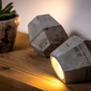 Concrete spotlight with geometric crystal shape design, for laying on the floor or shelve. The lampshade provides a soft beam of light for any of its faces directions, using lamp (LED lamp included).