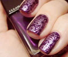 Purple nails with silver flowers.