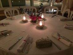 Gorgeous table settings from our most recent wedding. Live floral centerpieces and small fishbowls with candles.