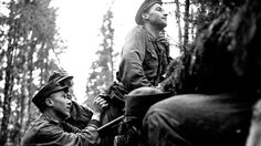 A Finnish soldier is hoisted above a trench by two comrades to get a better view of the position of Soviet troops during the Finnish-Soviet Continuation War. Near Lake Ladoga, Karelia. April 1942.