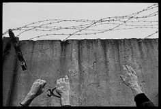 Hands of East and West Germans are seen tearing down barbed wire from the top of the Wall at the newly-opened Ostpreussendamm Strasse checkpoint in Berlin, West Germany, 1989, by James Nachtwey