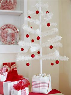 A Snowy Side Table:   This 36-inch white tree found at a crafts store is simply decorated with tiny red ornaments. The pot is wrapped with a folded dinner napkin secured with a belt of ribbon. A new dishtowel or wrapping paper would work just as well. Mini pearl-like baubles fill in around the base of the tree.