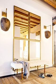 Stacked brass mirrors flanked by (ugly) sconces + a white bench
