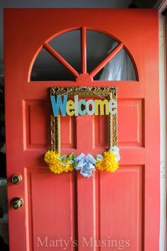 Create a warm welcome for guests with this easy and inexpensive front door wreath using a repurposed yard sale picture frame, silk flowers and wooden sign.