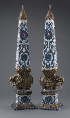 A Pair of blue & white with red details porcelain and chiseled ormolu obelisks after the Elephant Obelisk of Santa Maria Sopra Minerva in Rome by Bernini. The obelisks decorated in Iznik taste ; each supported by an elephant resting on a base of the same foliage decorative frieze h. 65 cm