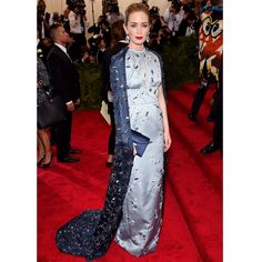 Emily Blunt in PRADA at the 2015 Metropolitan Museum of Art's Costume Institute Gala.  Emily Blunt chose a PRADA steel blue nylon duchesse keyhole neckline gown with touches of crystal and glass bead ramage embroidery, continuing fully onto the jewel encrusted navy organza cape.  She finished the look with a navy raso clutch with a crystal clasp closure. #PradaCelebs