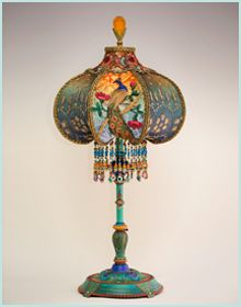 Beautiful and unusual 1920s era table lamp with peacock feather motifs has been hand painted and holds a Peacock & Roses silk and beaded shade. The shade is ombré dyed in jewel tones of raspberry and amber into green and blue tones and µhas alternating panels of dyed burnout velvet and styled antique net lace with feather motifs. The shade has hand-beaded fringe in beautiful jewel tones.