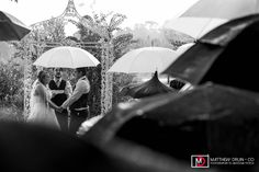 Bride and groom getting married with umbrellas at ceremony in the rain from a destination rainy day wedding in Orlando, Florida from destination Atlanta wedding photographers Matthew Druin + Co. Photography.