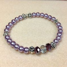 This pretty and elegant Memory Wire Bracelet is made using Glass Pearls in a pale shade of Lilac. It has three fire polished Czech Glass faceted