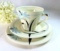 Fabulous art deco trio of cup, saucer and teaplate produced by the MYOTT Pottery in Stoke-on-Trent, England, between 1930 and 1942. Hand-painted  Cornflower blue, silvery-grey and black floral design (hva)