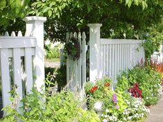 Gorgeous cottage gate design, love the flowers on the street-side of the fence to soften the effect of the tall privacy fence.