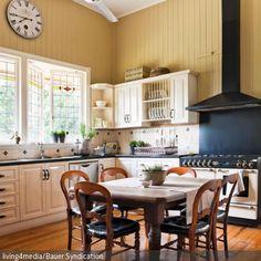 Um Gemütlichkeit und Landhaus-Charme in die Wohnküche zu bringen, wurde der Raum mit einer Holzvertäfelung ausgekleidet. Eine moderne, schwarz-weiße Küche setzt …