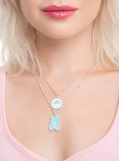You'll be happy wearing this Grumpy Bear necklace set. We know, it's ironic. The silver tone necklace set includes one chain with a Grumpy Bear enamel pendant. The second  Care Bears  necklace features a circular rain cloud belly badge pendant.       Alloy  Imported