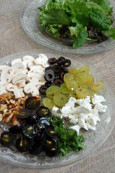 Ingrédients :  Un peu de persil Quelques bouts de chèvre Des olives noires Des raisins blancs et noirs De la salade Des champignons de Paris Quelques noix De l'huile d'olive pour assaisonner