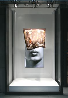 "Japanese designer, Tokujin Yoshioka designed an understated window display to feature iconic Hermés scarves—a timed video of a woman's face, softly blowing at a scarf. The hanging scarf moves slightly with the help of hidden fans. Tokujin Yoshioka, the ""designer of sensations,"" is fond of accidental happenings. He simply suspends an iconic garment in the air, presents it as a real-life object and prepares you for the unexpected."