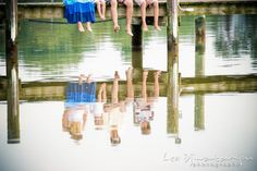 Feet and legs hanging from pier, with the family's reflection on the water.