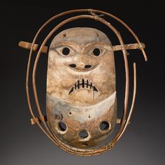 """YUP'IK OR KUSKOKWIM RIVER POLYCHROME WOOD MASK    of oval form, encircled by a double frame of wood rods and hide bindings, with a series of three holes, surmounted by a face, with down turned mouth, jagged teeth, flaring oval nostrils,and circular eye rims, painted with a pair of goggles and other (faded) details; the back with a wood """"bite."""""""