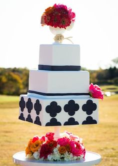 A geometric navy blue and white cake by Sugar Bee Sweets. Floral accents by Lush Couture Floral. Photo by Tracy Autem Photography. #wedding #cake #navy #white #floral #accent #geometric #pattern #print #square