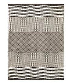 Naturvit/Antracitgrå. En stor matta i vävd bomullskvalitet med tryckt mönster på ovansidan.