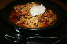 Original Taco Soup CrockPot Recipe --..........add  -- 4 cans of beans (pinto, black, kidney)  --2 cans of corn  --1 large can of diced tomatoes  --1 can tomatoes w/green chiles  --1 packet taco seasoning  --1 packet ranch Hidden Valley  --1 lb browned hamburger  --1 chopped onion..High 5 hrs...top with  --shredded cheese and sour cream