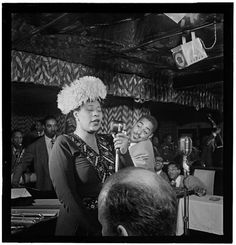 William P. Gottlieb: Ella sings to the crowd while Dizzy Gillespie listens, 1947. Portrait of Ella Fitzgerald, Dizzy Gillespie, Ray Brown, Milt (Milton) Jackson, and Timmie Rosenkrantz, Downbeat, New York, N.Y., ca. Sept. 1947, n.d. Prints and Photographs Division, Library of Congress.