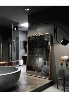 baño, con bañera exenta frente a espejo restaurado, cabina de ducha cerramiento de vidrio, suelo microcemento, muebles obra, color gris diferentes tonalidades