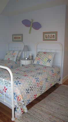 Twin iron beds with quilts