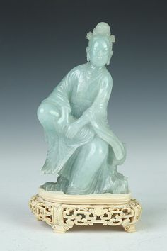 CHINESE CELADON JADE FIGURE OF GUANYIN. Qing Dynasty. Seated at ease, ivory reticulated base - 6 1/2 in. high.