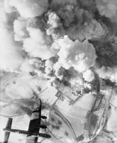 An Avro Lancaster of No. 625 Squadron RAF flys over the smoke-covered target during a daylight attack on German armour and troops concentrations at Sankt-Vith, by 294 aircraft drawn from most of the Bomber Groups of the RAF.