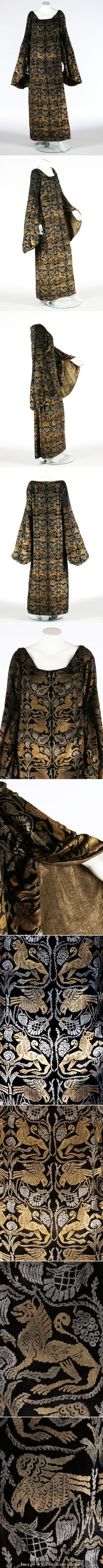 A Maria Gallenga stencilled velvet medieval style dress, circa 1925. the black silk velvet printed overall in gold and silver with birds and lions, with gold lame lined hanging sleeves. KTA