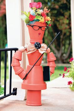 Create this distinguished dame by stacking up an assortment of clay pots and saucers. Give the lady some limbs by stringing grapevine wire through eight small pots and two wooden balls, as shown. Then glue her together with permanent adhesive, and dress her up with some telling teacher details.
