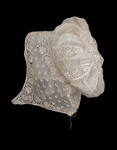 Woman's embroidered mull cap with a puffed crown and chin pendants; embroidered in pattern of semicircular rows of eyelets around leafy sprigs with rows of small V-shaped motifs; embroidered circular piece at top of crown with gathered insertions of plain fabric between embroidered bands below; fine drawstring at nape ofneck