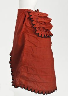 Woman's Cage Crinolette Petticoat | LACMA Collections England, 1872-1875 Costumes; underwear (lower body) Wool plain weave, cotton plain weave, cotton-braid-covered steel, cotton twill tape, and wool-braid trim Center back length: 35 in. (88.9 cm); Diameter: 25 in. (63.5 cm)