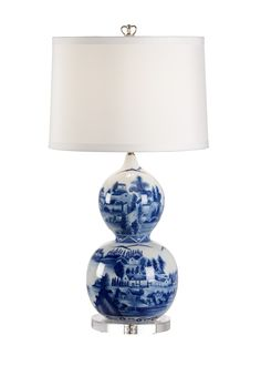 This lovely table lamp is made with porcelain and features a scenic design in blue and white. The lamp has an acrylic base and comes with a white shade. The lamp measures 30