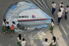 Students look at a giant 3D drawing of the missing Malaysia Airlines flight MH370 on the grounds of their school in Manila.