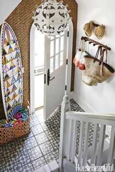 Designer Colleen Bashaw hoped to add naturaltexture in a beach house'sentryway without covering up the custom-patterned cement tile. So she installed a sisal rug on the wall. Pretty smart. Click through for more genius foyer ideas.