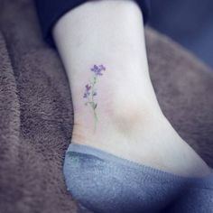 Watercolor style sweet pea flower tattoo on the ankle. Tattoo...