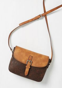 At no extra cost, this faux-leather purse flaunts a sassy southern vibe! With a deep brown, tooled body and a distressed sienna flap - flaunting a decorative silver buckle and a snap closure - this rustic crossbody is the 'lone star' of your ensemble.