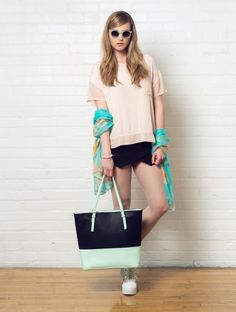 Fleur is wearing a C'est Moi pink pocket tee, black skort, a 3-in-1 tote, and a mint feather print scarf