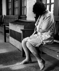 Jerry Cooke - A female patient, whose are restrained in a straightjacket, sits alone on a bench and cries in a mental institution, Youngstown, Ohio, 1946. There are open, untreated sores on her leg. °