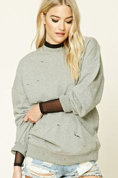 A heathered knit sweatshirt featuring an oversized silhouette, distressed design, French terry cloth lining, ribbed trim, a round neckline, and long sleeves.