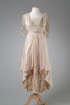 Back: SILK TAFFETA EVENING GOWN, 1914 1914 Pink silk taffeta evening gown with a pannier effect on the hip, and trimmed with machine embroidered net. Accented with crushed cording flower trim. This garment was owned by Matilda Dodge Wilson (October 19, 1883 – September 19, 1967),who was the wife of John Francis Dodge (October 25, 1864 – January 14, 1920), co-founder of the Dodge Motor Car Company in Detroit, Michigan. Wayne State University Library Digital Collection